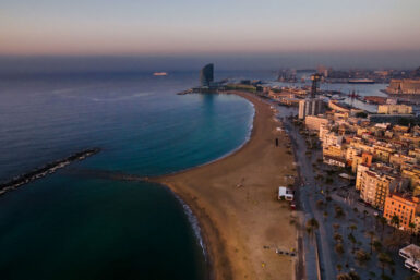 Eine Luftaufnahme mit Drohne vom Sonnenaufgang über dem Meer in Barcelona