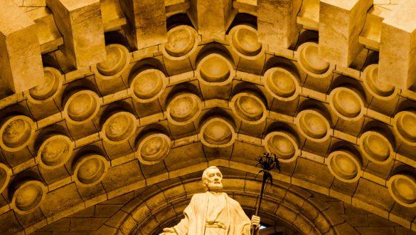 Statue eines Heiligen über der Eintrittstür im Kirchenschiff der Sagrada Familia.