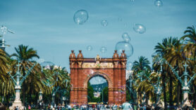 Seifenblasen schweben vor dem Arc de Triomf in Barcelona.