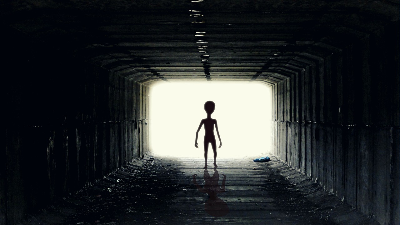Sillhouette eines Außerirdischen der durch einen Tunnel läuft