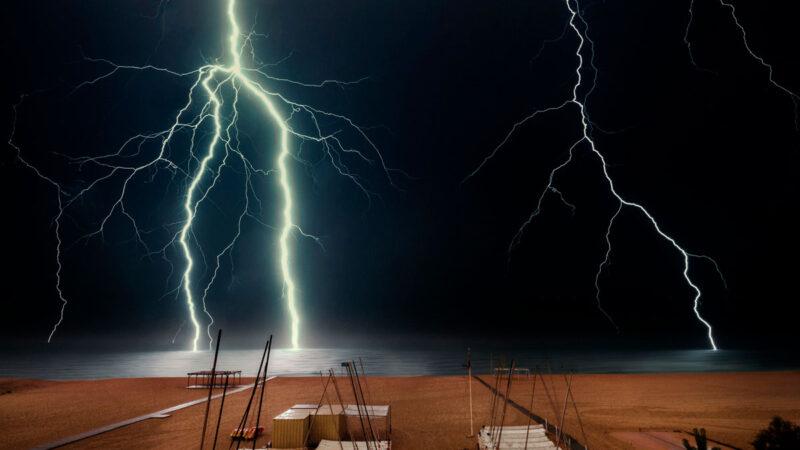 Gewitter am Strand, mehrere Blitze schlagen im Meer ein.