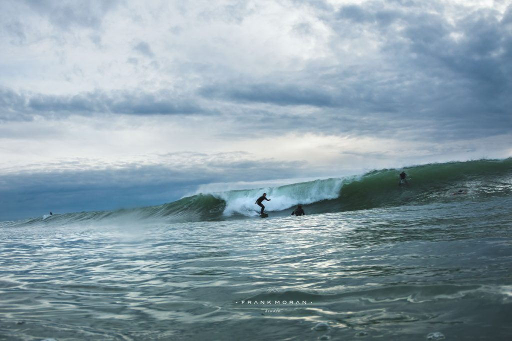 Drei Surfer am Wellenreiten.