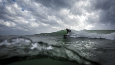 Ein Surfer beim Wellenreiten an einem windigen Tag.