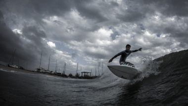 Ein Surfer beim Wellenreiten an einem bewölkten Tag.