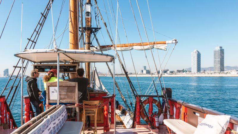 Oberdeck des Piratenschiffs, drei Steuermänner und Blick auf den Strand von Barcelona.