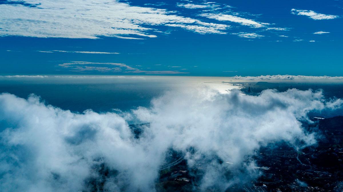 Sicht auf Barcelona und das Mittelmeer durch eine Wolkendecke.