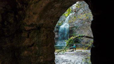 Frau und schwarzer Hund vor Wasserfall, durch Steintüre fotografiert.