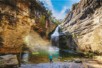 Frau steht vor Wasserfall, von der Seite fallen Sonnenstrahlen durch Öffnung im Gestein.