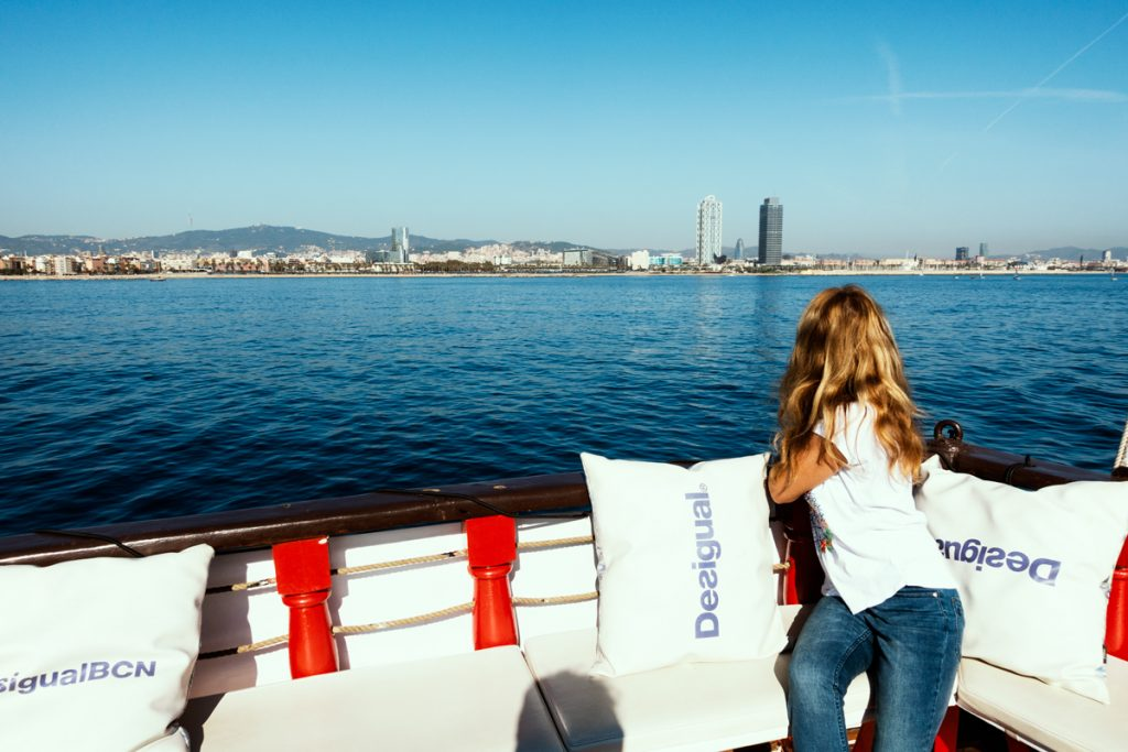 Frau blickt von Schiff über das Meer auf die Skyline von Barcelona.