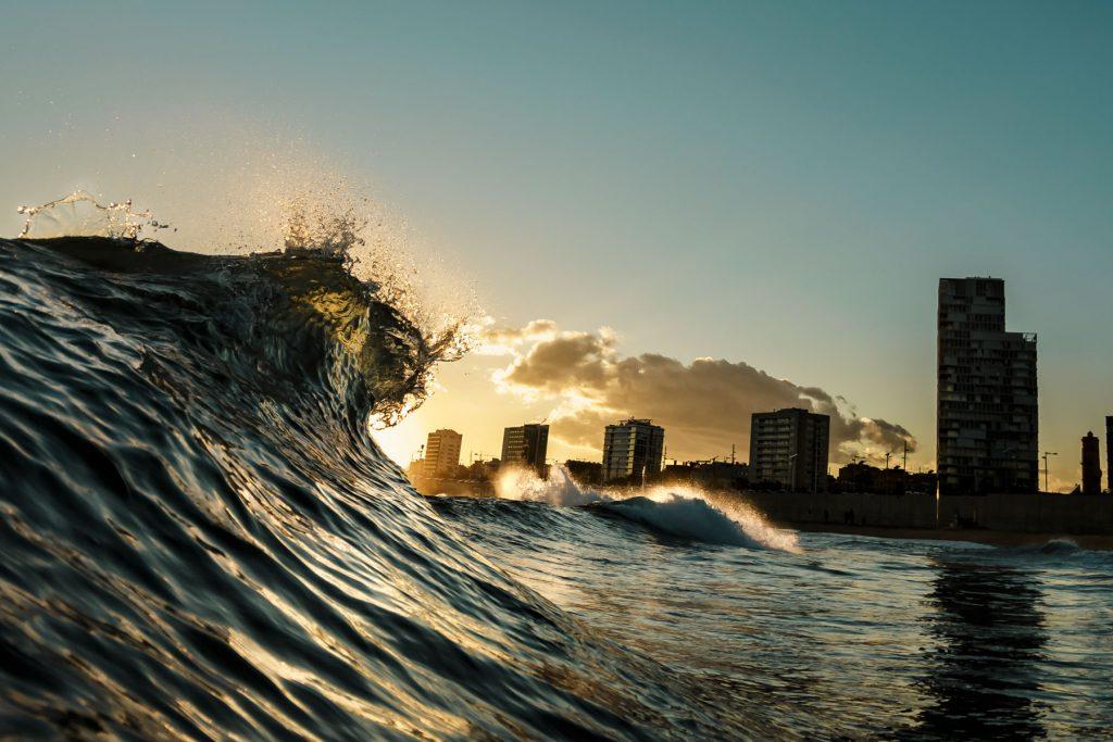 Eine auf die Hochhäuser von Barcelona zuschnappende Welle aus dem Wasser bei Dämmerung fotografiert.