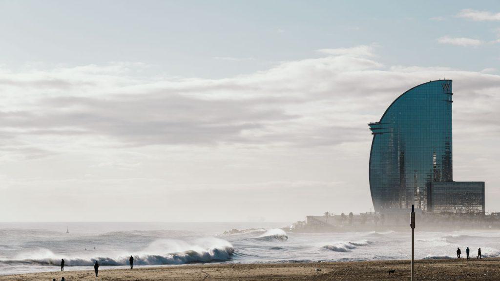 Das bewegte Meer am Strand von Barceloneta im Winter, das Hotel W im Hintergrund.