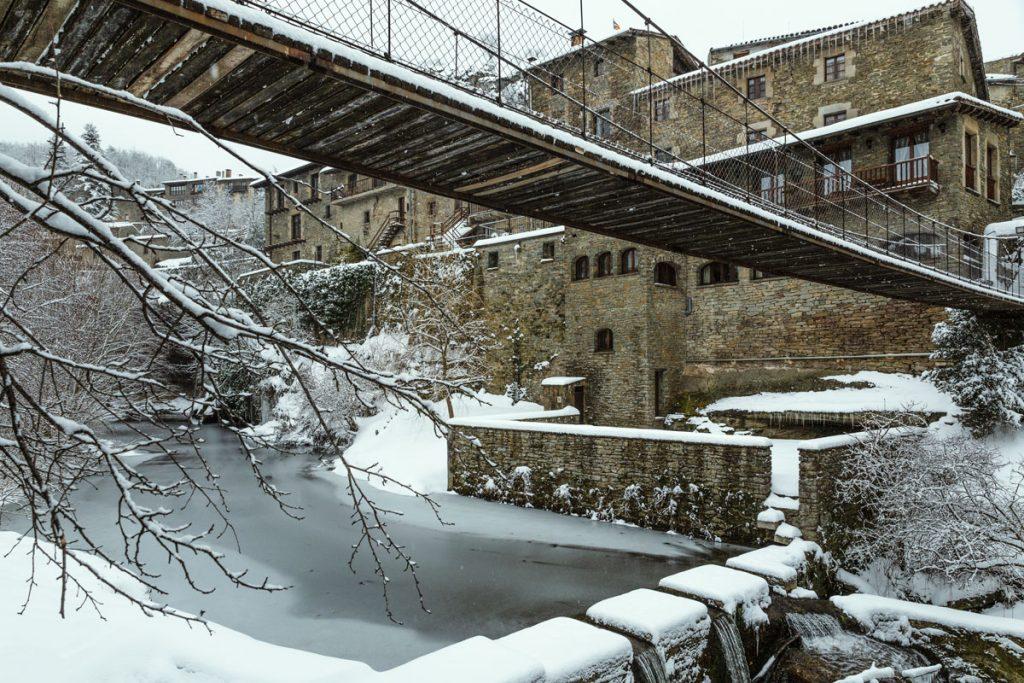 Vereister Fluss unter Hängebrücke, die ins Dorf führt.