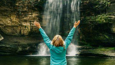 Frau steht mit ausgestreckten Armen vor einem Wasserfall.