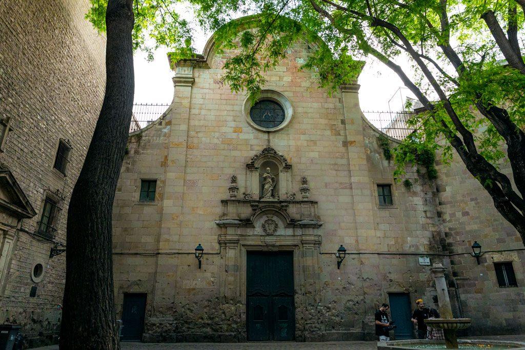 Schattiger Platz mit barocker Kirche und Brunnen.