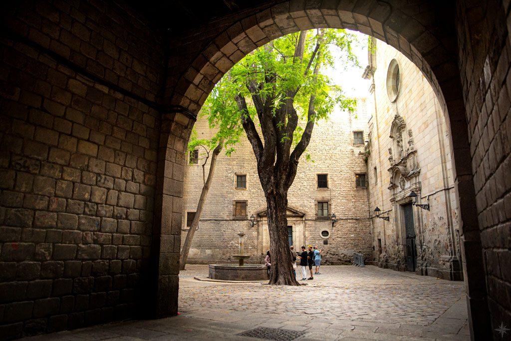 Blick auf romantischen Platz mit Brunnen und Baum in der Mitte.
