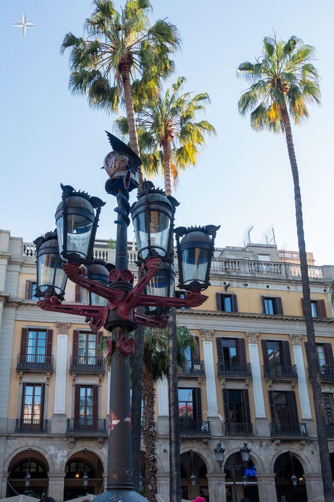 Von Antoni Gaudi geschaffene Laterne mit Palmen im Hintergrund.