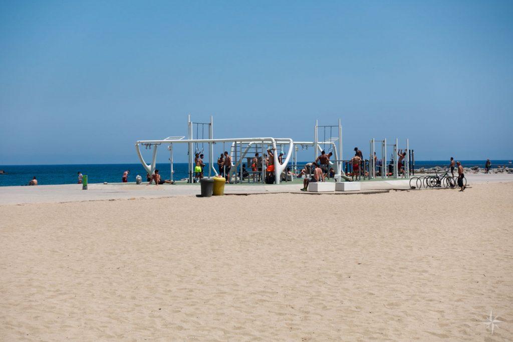 Muskelbepackte Männer am Freiluft Fitnessstudio am Strand von Barcelona.