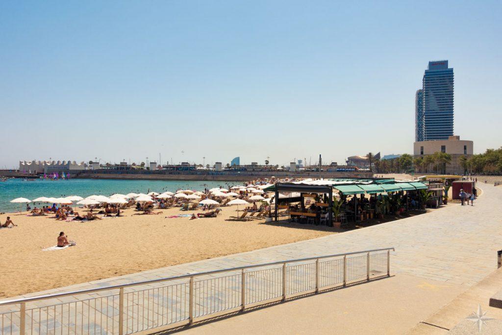 Strandbar, Liegestühle und Sonnenschirme am Strand von Barcelona, mit dem angrenzenden olympischen Hafen.