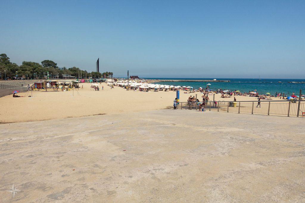 Menschen, Sonnenschirme, Volleyballnetze und Strandbars am Strand von Barcelona.
