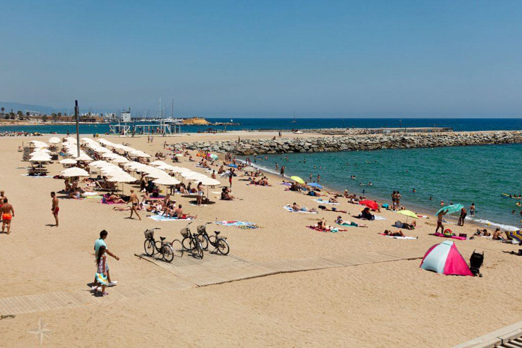 Sonnenschirme, Sonnenliege und Fitnessecke am Strand von Barcelona.