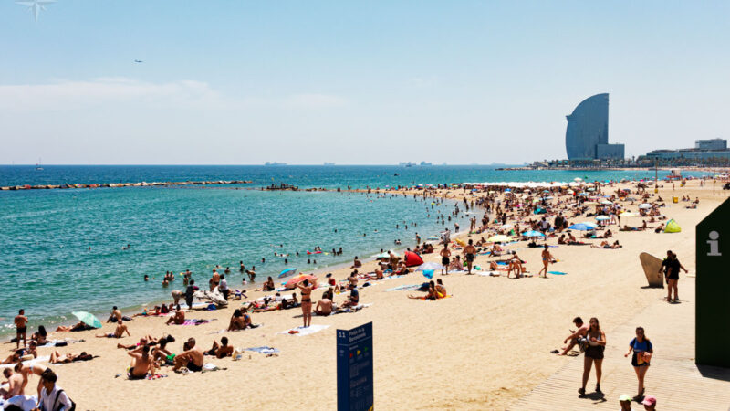 Die mit Menschen gefüllten Strände Barceloneta und Sant Miquel mit dem Hotel W im Hintergrund.