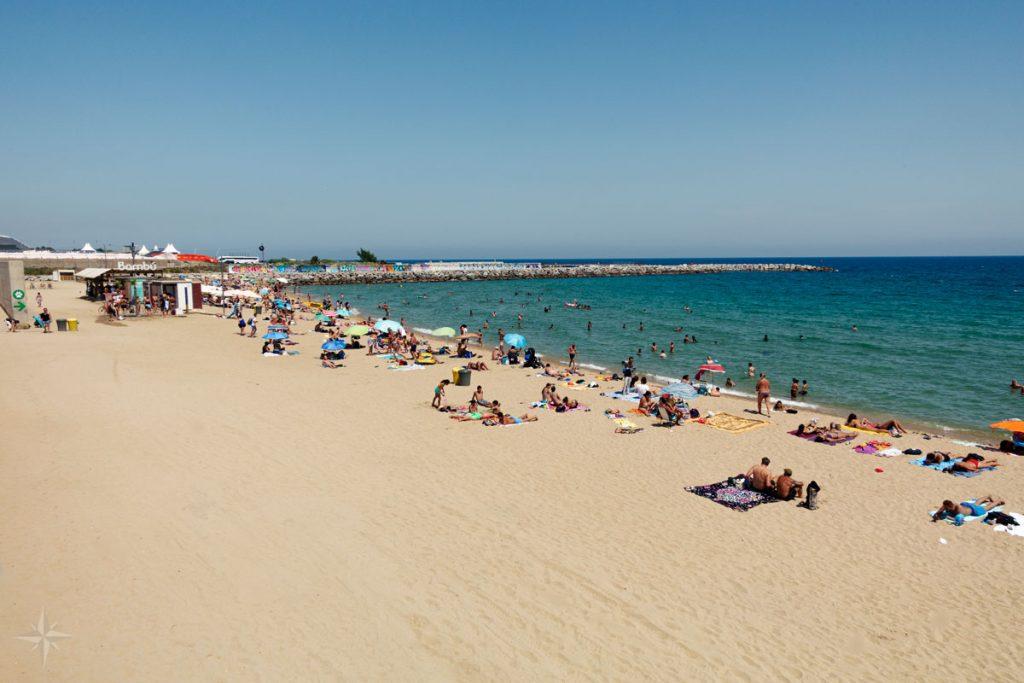 Der mit Handtüchern, Sonnenschirmen und Menschen gefüllte Strand Levante von Barcelona.