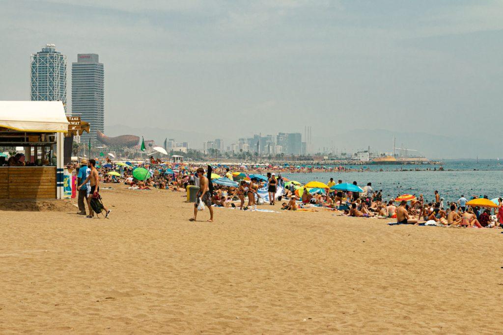Mit Sonnenschirmen und Handtüchern bedeckter Stadtstrand.