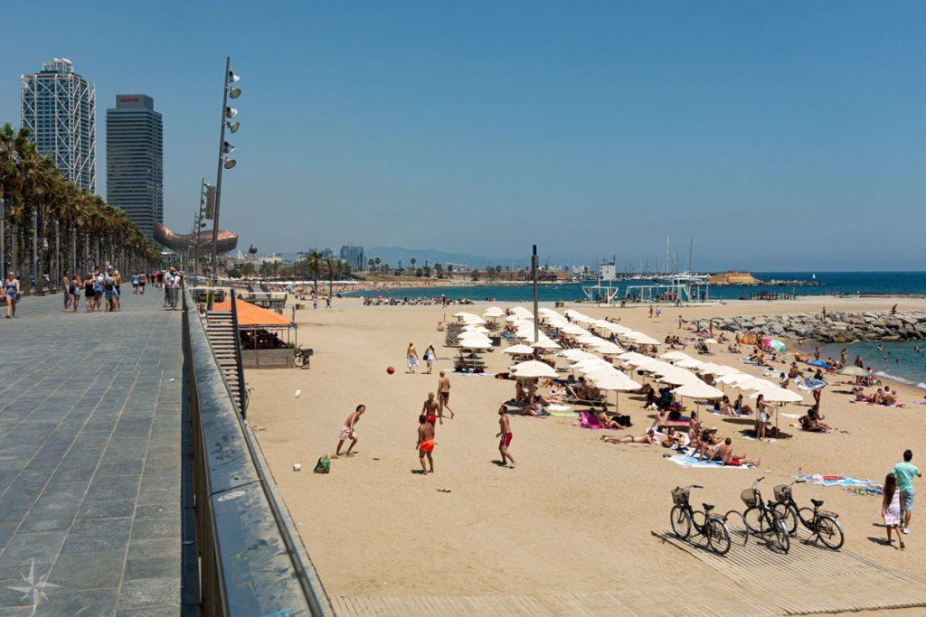 Der mit Menschen gefüllte Strand von Barcelona und die Strandpromenade.