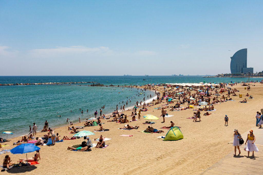 Der mit Menschen gefüllte Strand von Barcelona im Sommer, das an ein Segel erinnerndes Hotel W im Hintergrund.