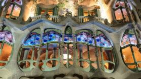 Ansicht der bunten Fensterfront der noblen Etage der beleuchteten Casa Batlló bei Nacht.