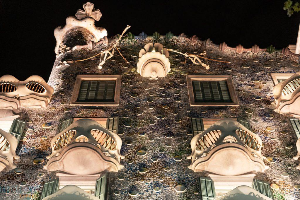 Die an Schädel erinnernden Balkone der beleuchteten Casa Batlló bei Nacht.