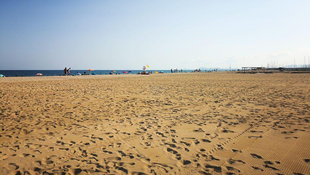 Weiter, von Fussspuren durchzogener Sandstrand, im Hintergrund ist die Silhouette von Barcelona zu sehen.