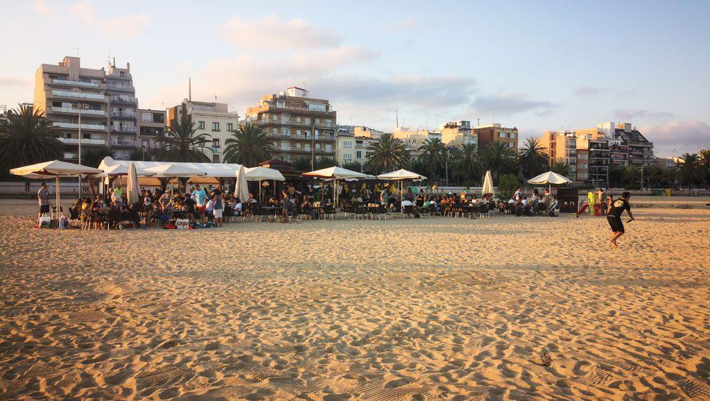 Eine mit Menschen gefüllte Strandbar mit Häusern im Hintergrund.