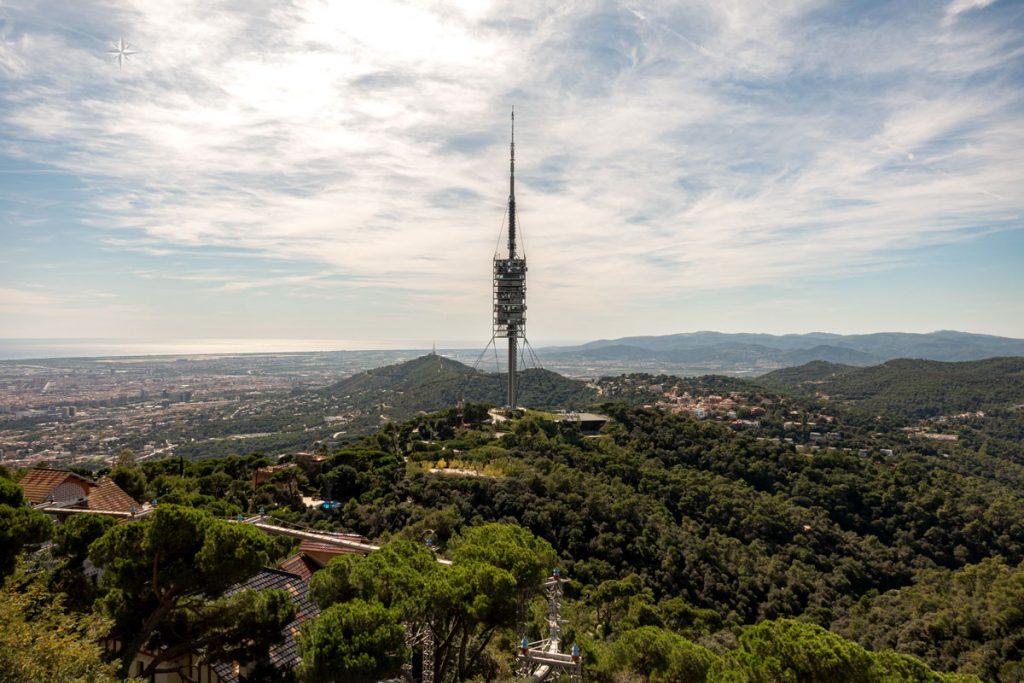 Der Fernsehturm von Barcelona ragt aus einer grünen, hügeligen Landschaft.