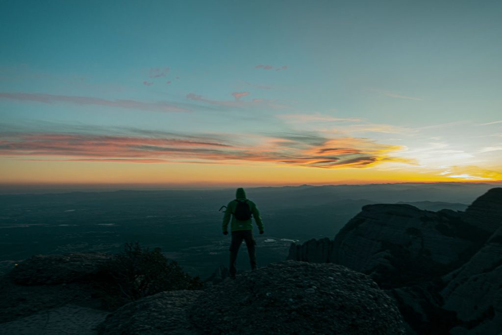 Mann blickt über das Tal des Montserrat bei Sonnenuntergang.
