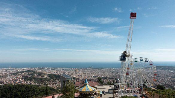 Aussicht über Barcelona vom Tibidabo mit Fahrgeschäften des Vergnügungsparks im Vordergrund.