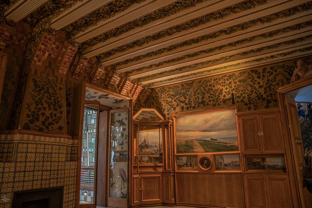 Das Esszimmer mit Kamin, hölzernen Schränken und Ölgemälden.