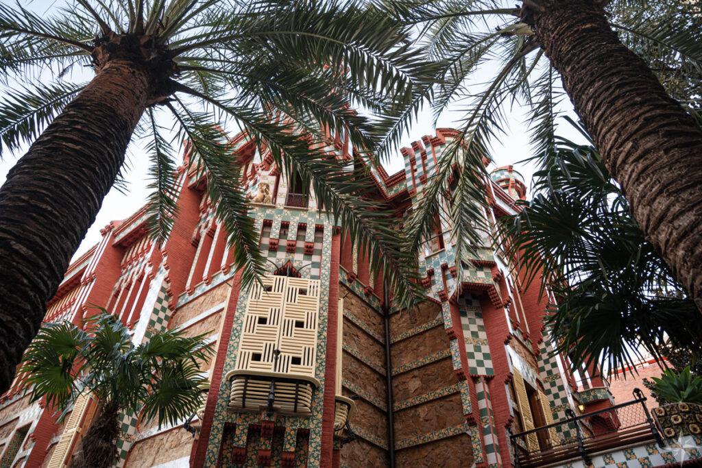 Die bunte Casa Vicens vom Garten aus betrachtet, mit zwei Palmen im Vordergrund.