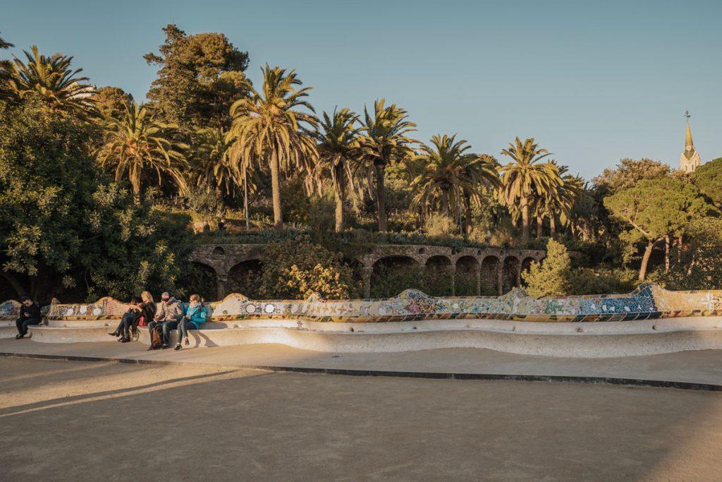 Besucher des Parks ruhen sich auf der Bank auf dem von Palmen gesäumten Plaça de Natura aus.