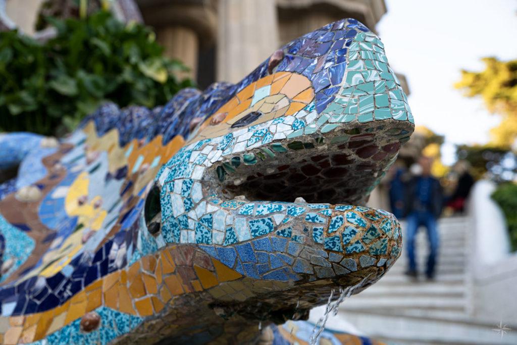 Nahaufnahme des mit bunten Keramikscherben besetzten Kopfes des Salamanders und Symbol des Park Güell.