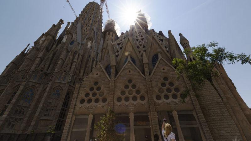 Die Sonne strahlt zwischen den Türmen der Sagrada Familia hervor, eine Frau zeigt mit dem Finger nach oben.