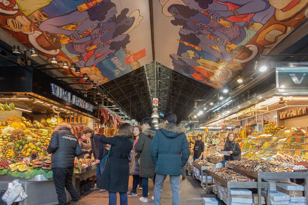 Besucher vor Ständen mit Obst in der Markthalle.