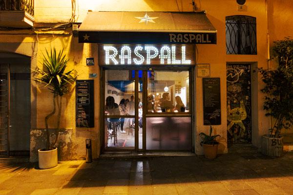 Die beleuchtete Tapas Bar Raspall abends von aussen.