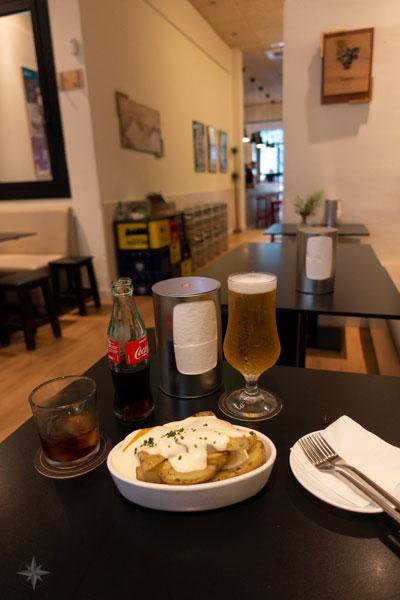 Tisch in einer Tapas Bar mit Getränken und einem Tapa Patatas Bravas.