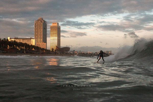 Ein Surfer in Barcelona mit den von der Abendsonne angeschienenen Torres Mapfre im Hintergrund.