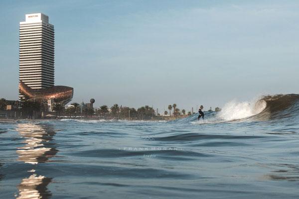 Ein Surfer vor dem Goldfisch am Strand von Barceloneta.