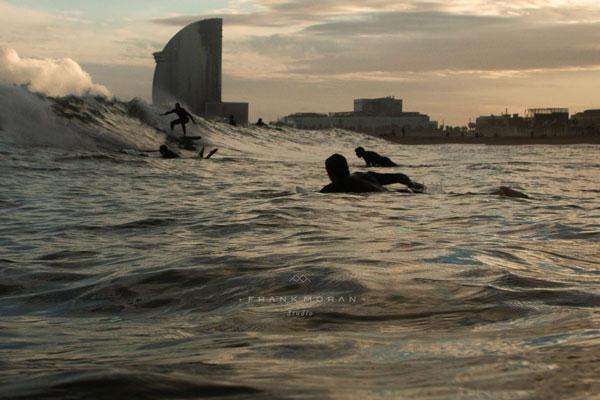 Einige Surfer im Wasser liegend warten auf die nächste Welle in Barceloneta.