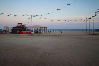 Eine mit Fähnchen dekorierte Strandbar im Sonnenuntergang.