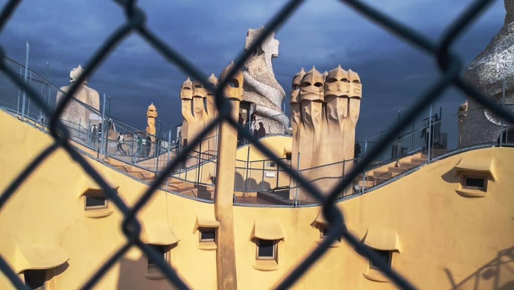 Die Dachterasse der Casa Batlló durch einen Zaun betrachtet.
