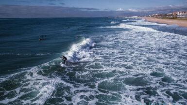Luftaufnahme auf das Meer und Surfer an der Küste von Maresme.